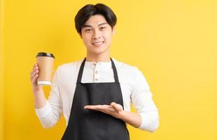 Porträt des männlichen Kellners mit Pappbecher in der Hand auf gelbem Hintergrund foto
