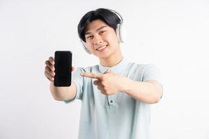asiatischer Mann trägt Kopfhörer und zeigt mit dem Finger auf das Telefon mit leerem Bildschirm foto