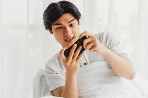 asiatischer Mann benutzt sein Handy, um Spiele im Bett zu spielen foto