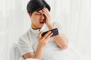 asiatischer Mann, der im Bett sitzt und Spiel spielt. der asiatische mann ist wütend, wenn er spiele am telefon spielt foto
