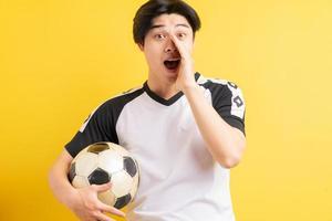 der asiatische mann hält den ball und schreit foto