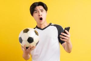 asiatischer Mann hält einen Ball und hält ein Telefon in der Hand foto