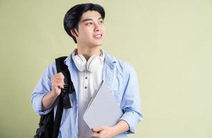 der männliche asiatische schüler hob seine augen nach links foto