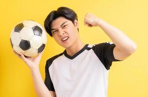 der asiatische mann hält den ball und zeigt triumphierend foto