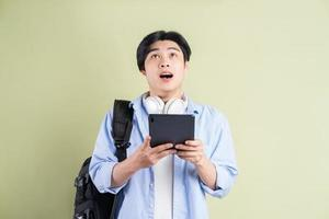 männlicher asiatischer Student, der das Tablet benutzte und mit einem überraschten Gesichtsausdruck aufsah foto