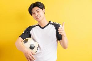 der asiatische mann hält den ball und zeigt die daumen hoch foto