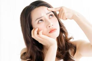 asiatische Frau sitzt Make-up vor Spiegel foto