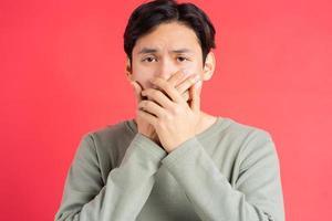 ein Foto eines gutaussehenden asiatischen Mannes, der sich den Mund zuhält, um das Geheimnis eines anderen nicht zu verpassen