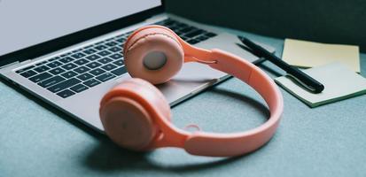 Bild eines Laptops mit weißem Bildschirm und rosa Kopfhörern daneben foto