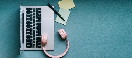 Top-Down-Bild von Laptop und rosa Kopfhörern foto