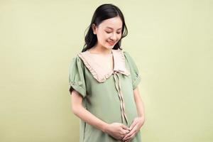 Schwangere Asiatin, die sich glücklich fühlt und sich auf die Geburt freut foto
