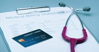 Bild von oben mit medizinischer Abrechnung, Kreditkarte und rosafarbenem Stethoskop auf grauem Hintergrund foto