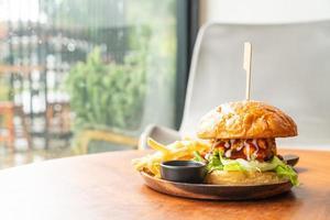 Rinderburger mit Käse und Sauce auf Holzteller foto