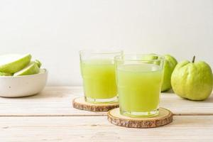 frisches Guavensaftglas mit frischen Guavenfrüchten auf Holztisch foto