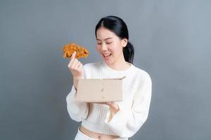 junge asiatische frau trägt einen pullover mit einem glücklichen gesicht und genießt es, gebratenes hähnchen auf grauem hintergrund zu essen foto