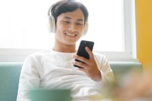 asiatischer Mann sitzt und genießt Musik foto