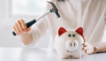 Frauenhand, die einen Hammer hält, um das Sparschwein auf dem Tisch zu zerbrechen, Geld und finanzielle Investitionen zu sparen foto