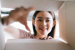 junge Asiatin öffnet das neue Paket, das nach Hause geschickt wurde foto