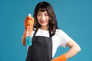ein Foto einer asiatischen Frau in einer Schürze und Handschuhen, die sich auf den Reinigungsjob vorbereiten