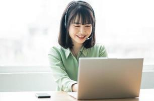 schöne asiatische kundendienstdame ruft kunden an, um produkte anzubieten foto