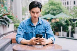 junger asiatischer Mann mit Smartphone im Café? foto