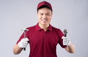 Bild des asiatischen Mechanikers auf grauem Hintergrund foto