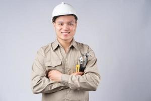 asiatischer Mechaniker, der mit verschränkten Armen auf grauem Hintergrund steht foto