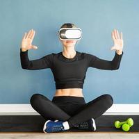 Junge blonde Frau in Sportkleidung mit Virtual-Reality-Brille, die auf der Fitnessmatte sitzt und das interaktive VR-Menü verwendet foto