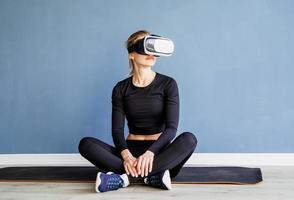 junge blonde Frau in Sportkleidung mit Virtual-Reality-Brille, die zu Hause auf der Fitnessmatte sitzt foto