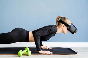 Junge blonde Frau mit Virtual-Reality-Brille macht zu Hause Liegestütze foto