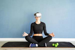 Junge blonde Frau in Sportkleidung mit Virtual-Reality-Brille, die auf Fitnessmatte meditiert foto