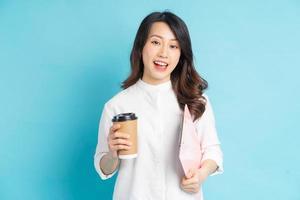 schöne asiatische geschäftsfrau, die papierkaffeetasse und broschüre in der hand hält foto