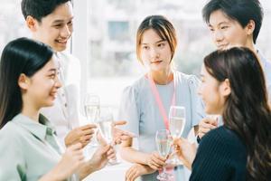 Asiatische Geschäftsleute der Gruppe stoßen zusammen an und plaudern auf einer Firmenfeier foto