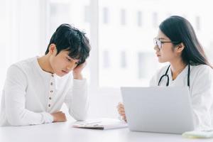 asiatische Ärztin überprüft den Gesundheitszustand des Patienten foto