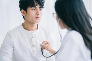 asiatische Ärztin hört auf den Herzschlag, um die Krankheit eines Patienten zu diagnostizieren foto