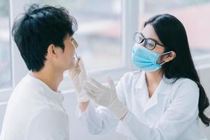 asiatische Ärztin, die die Zähne eines Patienten überprüft foto