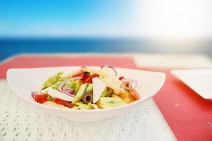 Vegetarischer Salat in Keramikplatte auf weißem Basttisch. foto
