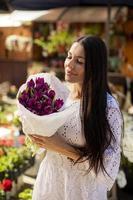 junge Frau kauft Blumen auf dem Blumenmarkt foto