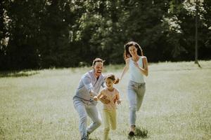 glückliche junge Familie mit süßer kleiner Tochter, die an einem sonnigen Tag im Park läuft foto