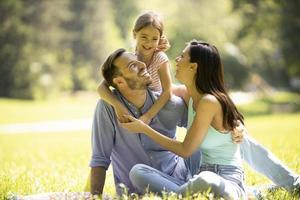 glückliche junge Familie mit süßer kleiner Tochter, die an einem sonnigen Tag Spaß im Park hat foto