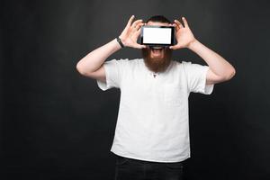 Porträt eines erstaunten bärtigen Mannes, der Tablette über den Augen mit weißem Bildschirm hält foto