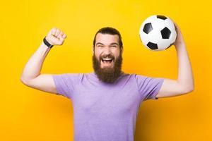 Erstaunter Mann mit Bart, der den Sieg schreit und feiert, Fan, der die Lieblingsmannschaft unterstützt und Fußball hält foto