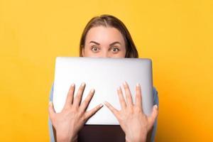 Foto von erstaunter junger Frau, die Gesicht mit Laptop bedeckt