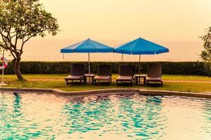 Liegestühle oder Poolbetten mit Sonnenschirmen um den Pool bei Sonnenuntergang foto