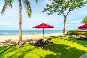 Sonnenschirm und Stühle mit Meerblick im Hotelresort für Urlaubsreisekonzept foto