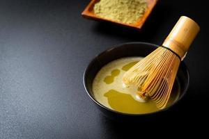 heiße Matcha-Grüntee-Tasse mit Grüntee-Pulver und Bambusbesen foto