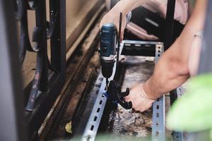 Do-it-yourself-Konzept verwenden Handwerker elektrische Bohrmaschinen, um alte Eisenteile zu montieren. Machen Sie ein Regal an Ihrem freien Wochenende. foto