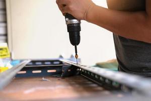 Do-it-yourself-Konzept verwenden Handwerker elektrische Bohrmaschinen, um alte Eisenteile zu montieren. mach ein regal an deinem freien wochenende foto