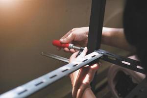 Do-it-yourself-Konzept verwenden Handwerker C-förmige Werkstücke, um alte Eisenteile zu montieren. mach ein Regal an deinem freien Wochenende foto
