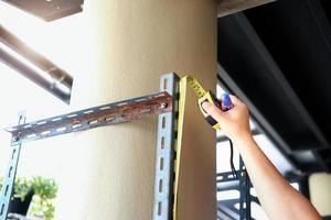 Heimwerker-Konzept Handwerker verwenden Höhenmaßbänder, um alte Eisenteile zu montieren. mach ein regal fürs wochenende foto